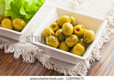 Olives are arranged in two white bowls with leaves on a wooden table - stock photo