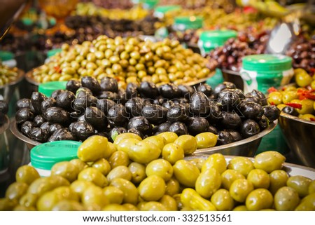 Olives at a market stall. A variety of types of olives. Green, black, Syrians and others. - stock photo