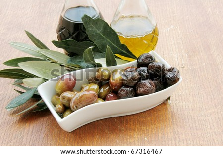 Olives ,balsamic vinegar and Olive Oil on a wooden table - stock photo