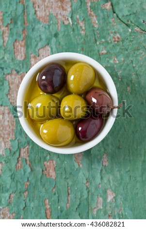 olives in a bowl on wooden surface - stock photo