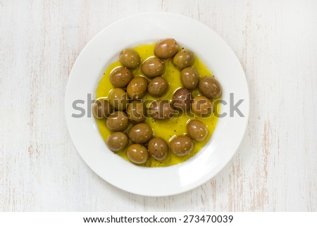 olives in olive oil on white plate