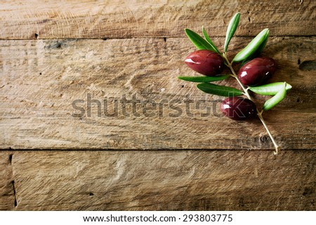 Olives on olive branch. Wooden table with olives - stock photo