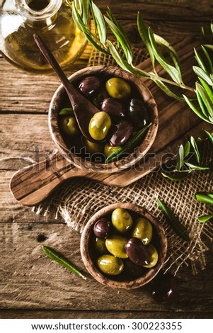 olives on olive branch. Wooden table with olives in bowl - stock photo