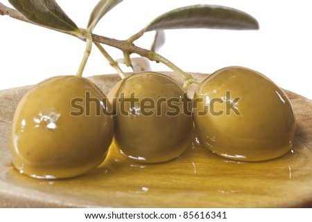 Olives soaked in olive oil on a wooden spoon
