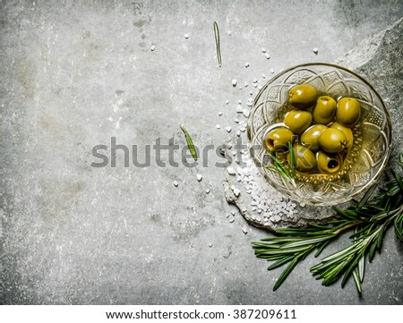 Olives with rosemary on a stone stand. On a stone background. - stock photo