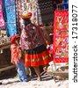 OLLANTAYTAMBO, PERU - 328 AUG 2008: Unidentified Peruvian Indian woman looking at colorful textiles,Ollantaytambo, Peru, South America - stock photo