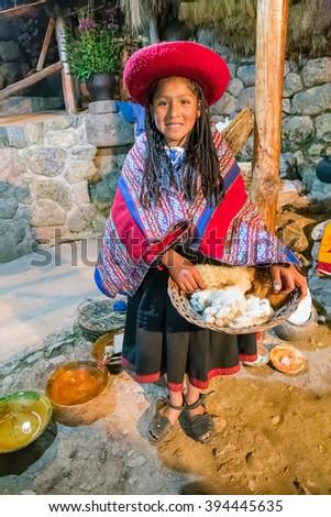 Ollantaytambo, Peru - circa June 2015: Girl in traditional Peruvian clothes holds a basket with Alpaca and Llama wool near Cusco, Peru - stock photo