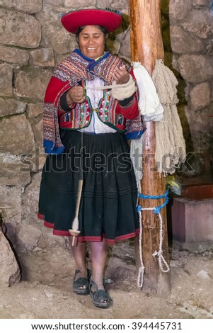 Ollantaytambo, Peru - circa June 2015: Woman in traditional Peruvian clothes makes yarn from Alpaca and Llama wool near Cusco, Peru - stock photo