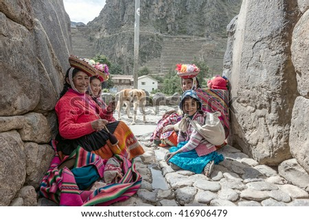 Ollantaytambo, Peru - december 18, 2014: Women and children in traditional Peruvian clothes break from posing with tourists