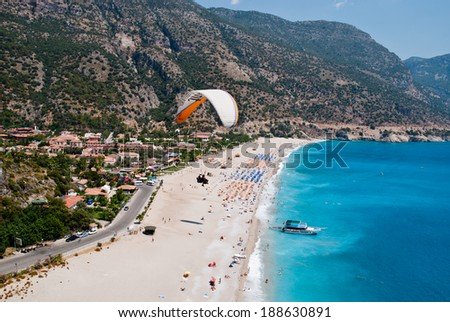 Oludeniz beach from paraglide: approaching to the landing point - stock photo