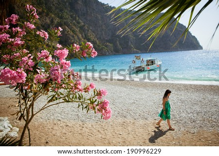 OLUDENIZ, TURKEY - JUNE 5: Girl in green dress strolls beach at Butterfly Valley on June 5, 2011 in Oludeniz, Turkey. Butterfly valley is a popular tourist spot only accessible by boat or steep hike. - stock photo