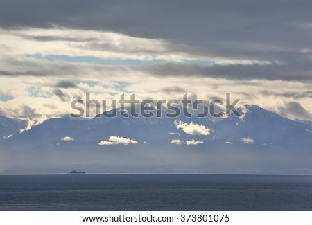 Olympic Mountains, Strait of Juan de Fuca. A freighter on the way out of the Strait of Juan de Fuca with the Olympic Mountains in the background. - stock photo