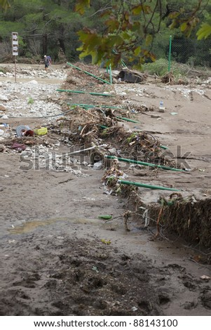 OLYMPOS, TURKEY - OCTOBER 14: A destroyed chain-link fence lies in ruins after flood disaster on October 14, 2009 in Olympos, Turkey. The floods destroyed roads, houses and swept away about 50 cars. - stock photo