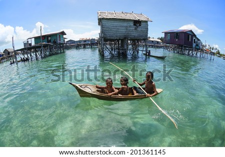 OMADAL ISLAND, SABAH, MALAYSIA - JUNE 6 : Unidentified Sea Bajau's children rowing a boat June 6th, 2014 in Omadal Island, Sabah Malaysia  - stock photo