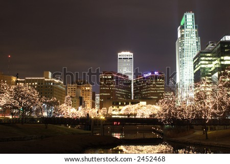Omaha Trees lit up in white Lights in the city with reflection in the water. - stock photo
