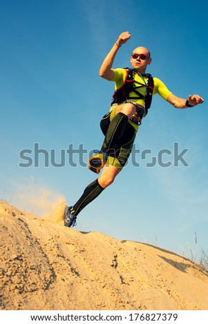 OMAN - JANUARY 30: Unidentified runner running in desert on extreme endurance marathon Transomania, on January 30, 2014. Runners reach the finish after running 300 km in mountains and desert. - stock photo