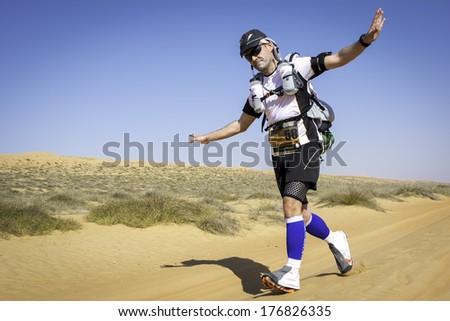 OMAN - JANUARY 29: Unidentified runner running in Omani desert on extreme marathon, on January 29, 2014. Transomania is one of the most extreme marathons ever, with 300 km in mountains and desert. - stock photo