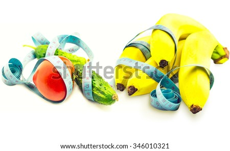 omato cucumber and banana wrapped in measuring tape on a white background