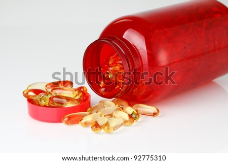 Omega 3 oil fish capsules with red plastic bottle on white background focused to the bottle - stock photo
