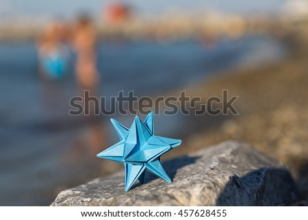 Omega star origami on the sea background - stock photo