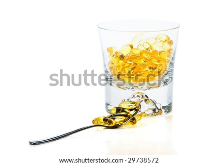 Omega-3 vitamins in glass  and teaspoon on white background - stock photo