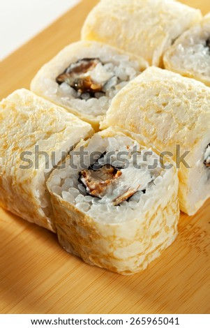 Omelet Maki Sushi - Roll made of Smoked Eel and Cream Cheese  inside. Japanese Omelet outside - stock photo