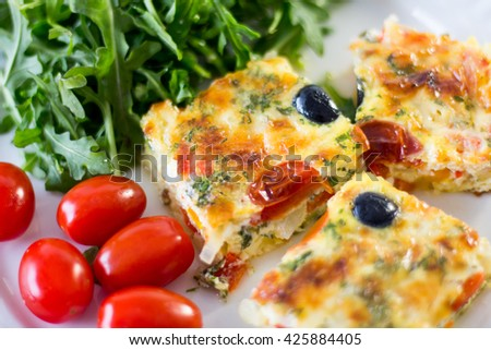 omelet on a white plate with salad and cherry tomatoes  - stock photo