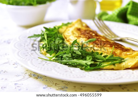 Omelet with cheese and arugula on a white plate on a light background.
