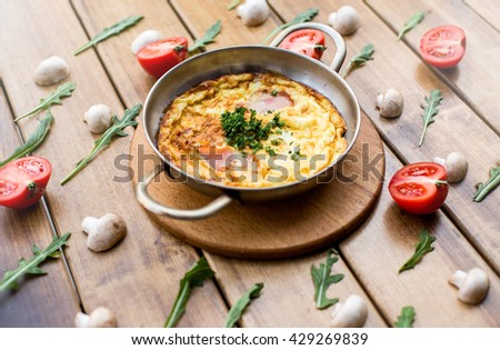 Omelet with mushrooms and tomatoes. Frittata in a frying pan - stock photo