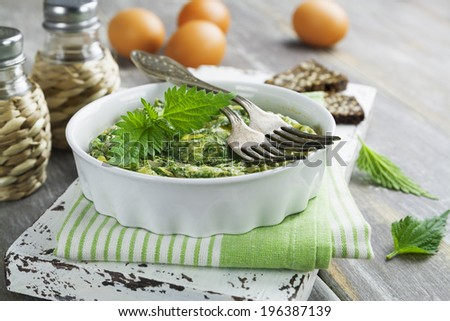 Omelet with nettles in the ceramic pot on the wooden table