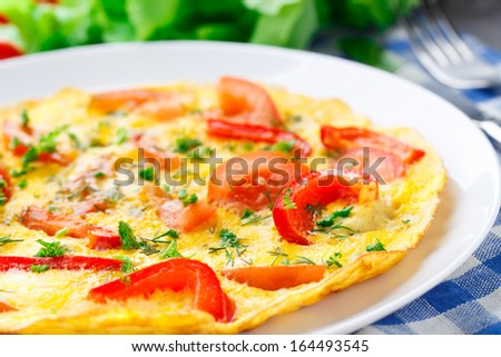 Omelet with paprika, tomato and herbs - stock photo