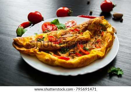 omelette in a plate on dark wooden background