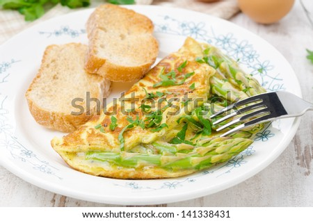 omelette with asparagus, greens and toast on the plate horizontal