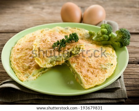 omelette with broccoli on green dish - stock photo