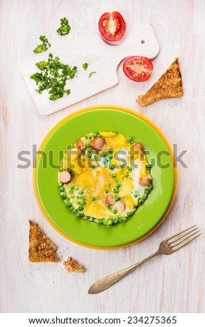 Omelette with green peas, potatoes and sausages serving on white wooden table with tomatoes, parsley and toast, top view - stock photo