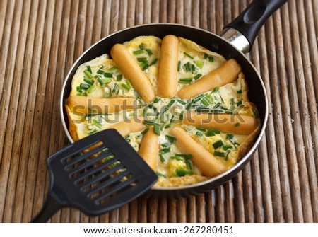 Omelette with sausages and herbs in frying pan on rattan table, shallow DOF - stock photo