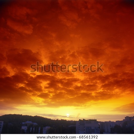 Ominous crimson sunset over a sity. Please see some similar pictures from my portfolio. - stock photo