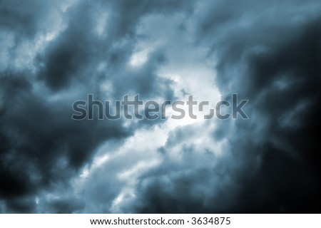Ominous dark thunderstorm clouds in the sky(cyan toned version) - stock photo