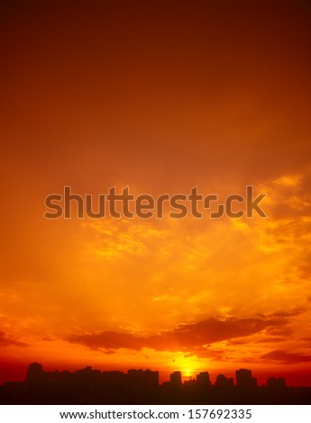 Ominous red sunset over a dark cityscape. - stock photo