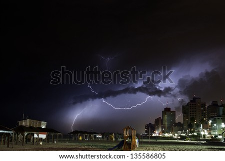 Ominous storm clouds cover the sky over Tel-Aviv Beach, shooting lightnings on a winter night. (slight grain, best used at small size)