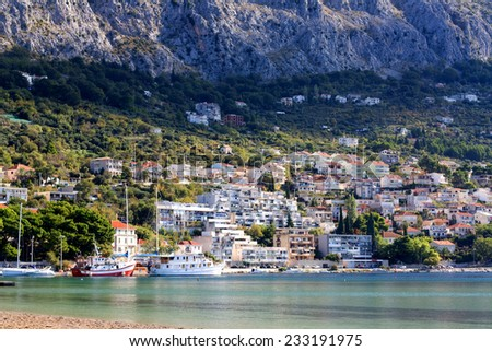 Omis, small town in Dalmatia. Eastern part of the town with houses and boats in the sea. - stock photo