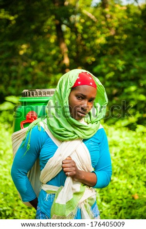 OMO, ETHIOPIA - SEPTEMBER 19, 2011: Unidentified Ethiopian beautiful woman carries a can of water on her back. People in Ethiopia suffer of poverty due to the unstable situation