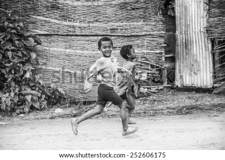 OMO, ETHIOPIA - SEPTEMBER 19, 2011: Unidentified Ethiopian boy and girl running. People in Ethiopia suffer of poverty due to the unstable situation