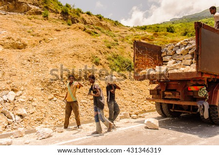 OMO, ETHIOPIA - SEPTEMBER 19, 2011: Unidentified Ethiopian boysput stones in the truck. People in Ethiopia suffer of poverty due to the unstable situation - stock photo