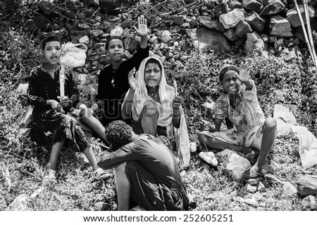 OMO, ETHIOPIA - SEPTEMBER 19, 2011: Unidentified Ethiopian girls sit on the grass. People in Ethiopia suffer of poverty due to the unstable situation