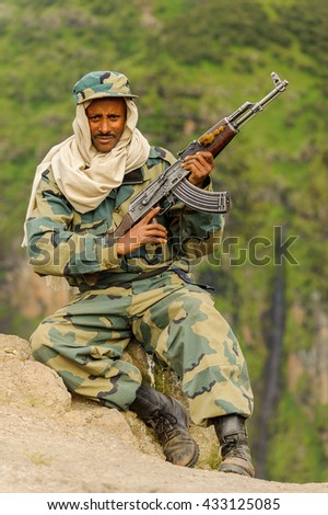 OMO, ETHIOPIA - SEPTEMBER 22, 2011: Unidentified Ethiopian military man with the gun near the waterfall. People in Ethiopia suffer of poverty due to the unstable situation