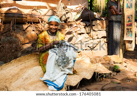 OMO, ETHIOPIA - SEPTEMBER 19, 2011: Unidentified Ethiopian old lady sewing on the ground. People in Ethiopia suffer of poverty due to the unstable situation - stock photo