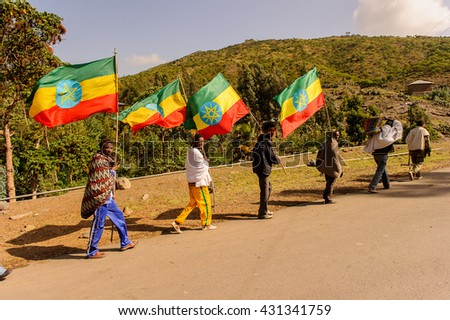 OMO, ETHIOPIA - SEPTEMBER 21, 2011: Unidentified Ethiopian people with national flags. People in Ethiopia suffer of poverty due to the unstable situation - stock photo
