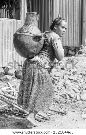 OMO, ETHIOPIA - SEPTEMBER 20, 2011: Unidentified Ethiopian woman carries a huge vase. People in Ethiopia suffer of poverty due to the unstable situation