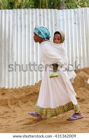 OMO, ETHIOPIA - SEPTEMBER 21, 2011: Unidentified Ethiopian woman in white tissue with a baby. People in Ethiopia suffer of poverty due to the unstable situation - stock photo